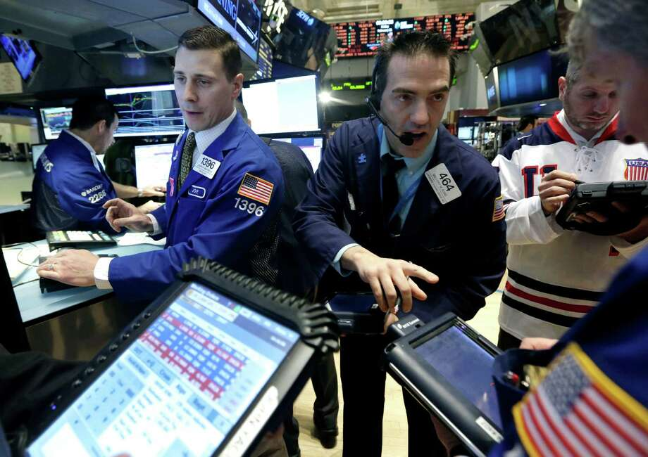 FILE - In this Friday, Feb. 21, 2014, file photo, trader Gregory Rowe, center, works at the post of specialist Joseph Mastrolia, left, on the floor of the New York Stock Exchange. The mood in financial markets steadied Monday, March 10, 2014, despite earlier big losses in Asia following disappointing Chinese and Japanese economic data. (AP Photo/Richard Drew, File) ORG XMIT: NYBZ199 Photo: Richard Drew / AP