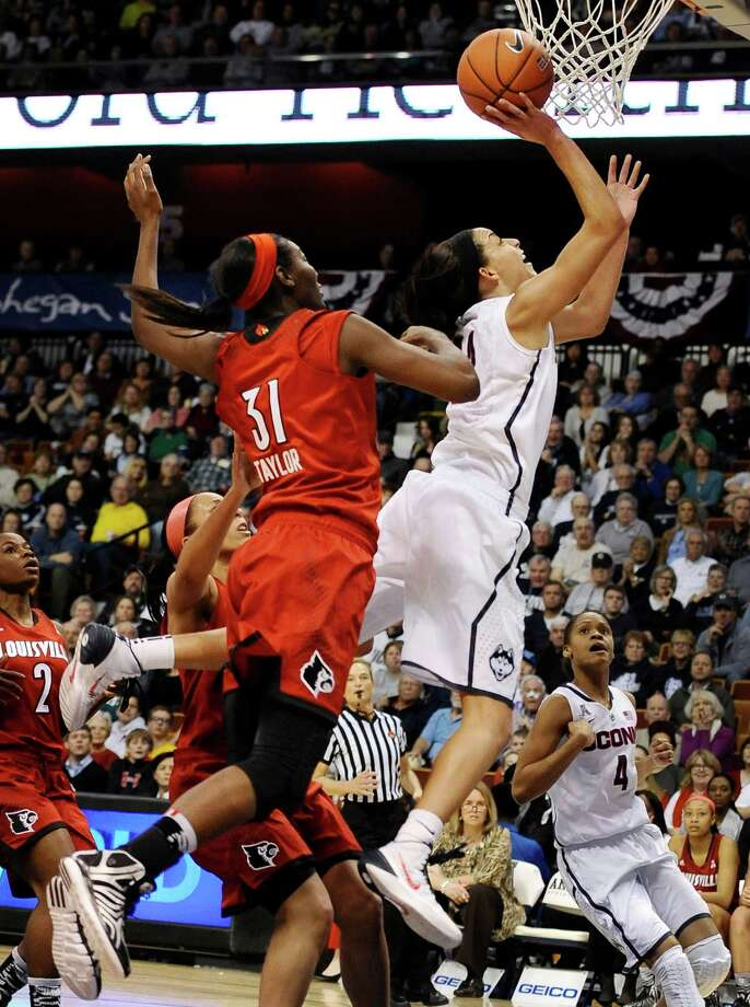 Louisville's Asia Taylor fouls Connecticut's Bria Hartley, right, is as she makes a basket during the first half of an NCAA women's college basketball game in the finals of the American Athletic Conference basketball tournament, Monday, March 10, 2014, in Uncasville, Conn. Photo: Jessica Hill, AP / Associated Press