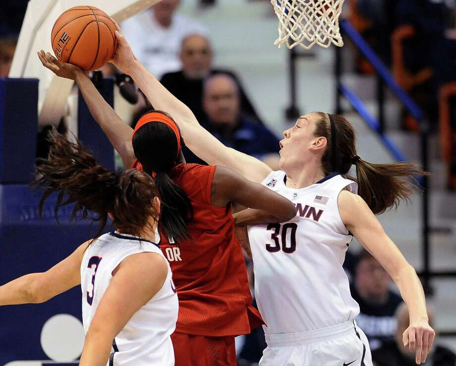 Connecticut's Breanna Stewart, right, blocks a shot by Louisville's Asia Taylor, center as Connecticut's Stefanie Dolson, left, defends, during the first half of an NCAA college basketball game in the finals of the American Athletic Conference women's basketball tournament, Monday, March 10, 2014, in Uncasville, Conn. Photo: Jessica Hill, AP / Associated Press