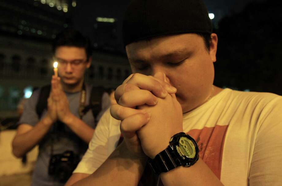 Men pray during a candlelight vigil in Kuala Lumpur, Malaysia, for passengers aboard missing Malaysia Airlines Flight MH370. The search operation involves several countries. Photo: Lai Seng Sin / Associated Press / AP