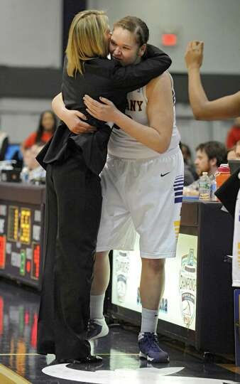 UAlbany head coach Katie Abrahamson-Henderson hugs Megan Craig after she fouled out of the game with