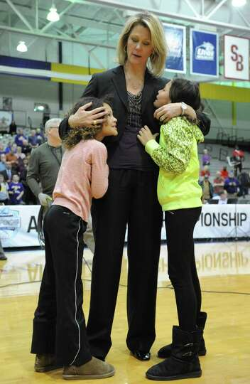 UAlbany head coach Katie Abrahamson-Henderson gets a hug from her daughters Brooklyn Henderson, 8, l