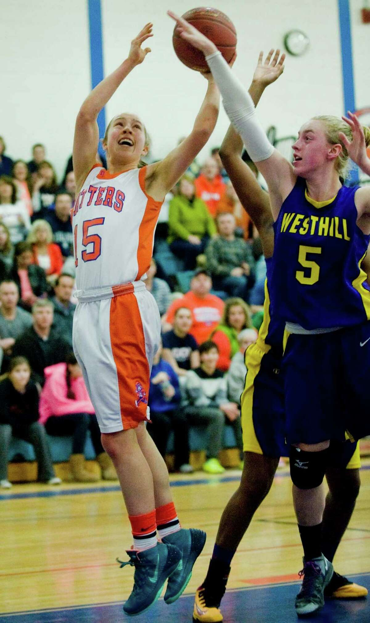Danbury High School Guard Rebecca Gartner tries to get off a shot as Westhill High School Forward Steph Roones tries to block the shot during the Class LL Girls Basketball Quarterfinals against Westhill High School, played at Danbury. Monday, March 10, 2014