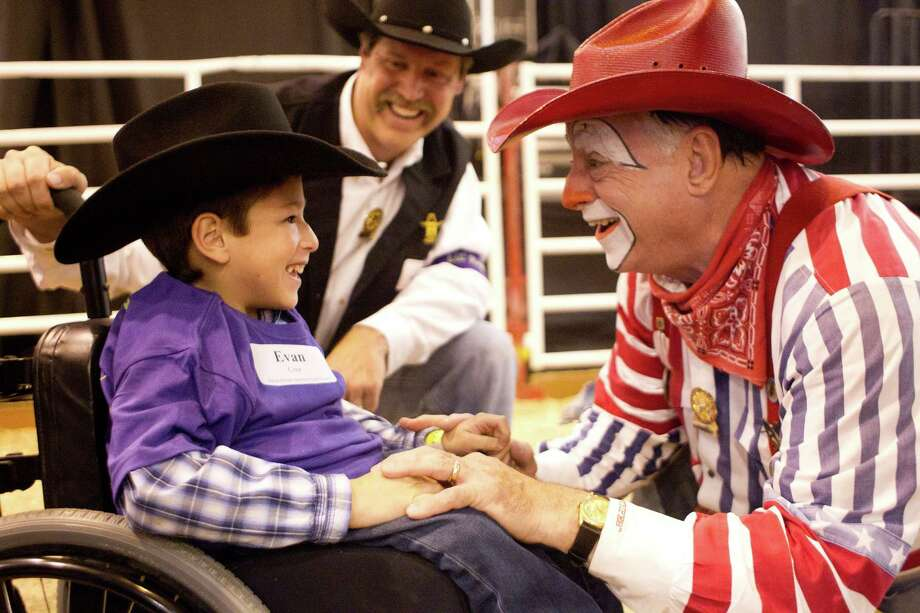 Steve Meeves, center, with the Rodeo Special Children's Committee watches as Stripes the rodeo clown brings a smile to 9-year-old Evan Cruz' face during the Lil' Rustlers Rodeo at the Houston Livestock Show and Rodeo at Reliant Center Monday, March 10, 2014, in Houston. The rodeo allows children with mental or physical disabilities to participate in a barrel race with stick horses, steer roping and bull riding on faux horses and bulls. Another Lil' Rustler Rodeo is scheduled for Wednesday, March 12 at 5 p.m. Photo: Johnny Hanson, Houston Chronicle / © 2014  Houston Chronicle