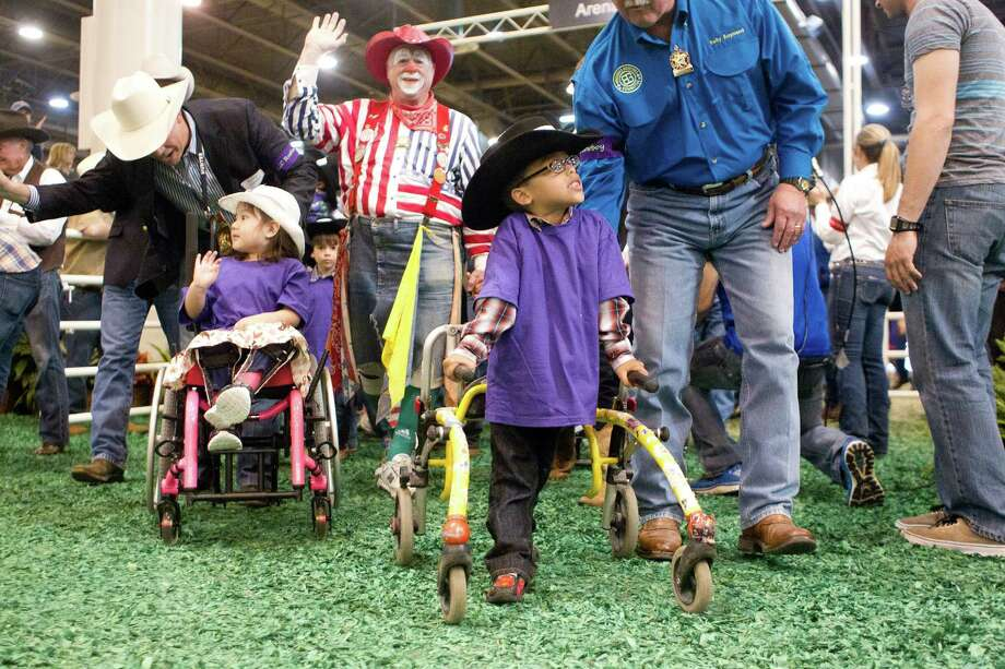 Children walk out to participate in the Lil' Rustlers Rodeo at the Houston Livestock Show and Rodeo at Reliant Center Monday, March 10, 2014, in Houston. The rodeo allows children with mental or physical disabilities to participate in a barrel race with stick horses, steer roping and bull riding on faux horses and bulls. Another Lil' Rustler Rodeo is scheduled for Wednesday, March 12 at 5 p.m. Photo: Johnny Hanson, Houston Chronicle / © 2014  Houston Chronicle