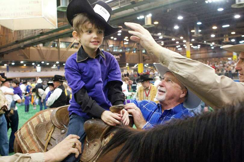 Kim Raymond with the Rodeo Special Children's Committee puts his little buddy Liam Brader, 6, on a h