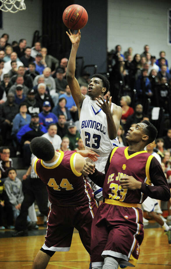 Bunnell's Isaac Vann scores over St. Joseph defenders Steve Hashemi, left, and Arkel Ager-Lamar in the first half of their opening round game in the Class L State Boys Basketball Tournament at Bunnell High School in Stratford, Conn. on Monday, March 10, 2014. Photo: Brian A. Pounds / Connecticut Post