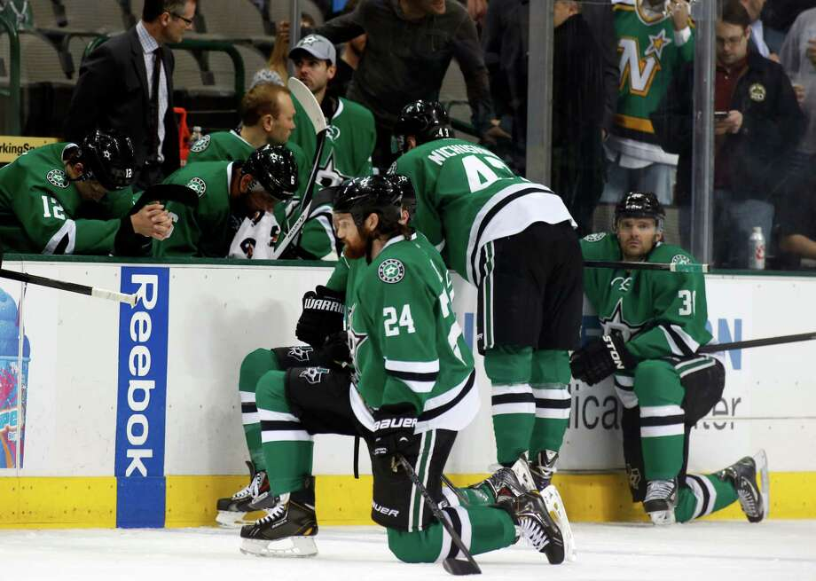 Dallas Stars right wing Alex Chiasson (12) bows his head on the bench as defenseman Jordie Benn (24) takes a knee on the ice after play was stopped in the first period of an NHL Hockey game against the Columbus Blue Jackets, Monday, March 10, 2014, in Dallas. Stars center Rich Peverly was taken to a hospital after a medical emergency. (AP Photo/Sharon Ellman) Photo: Sharon Ellman, Associated Press / FR170032 AP