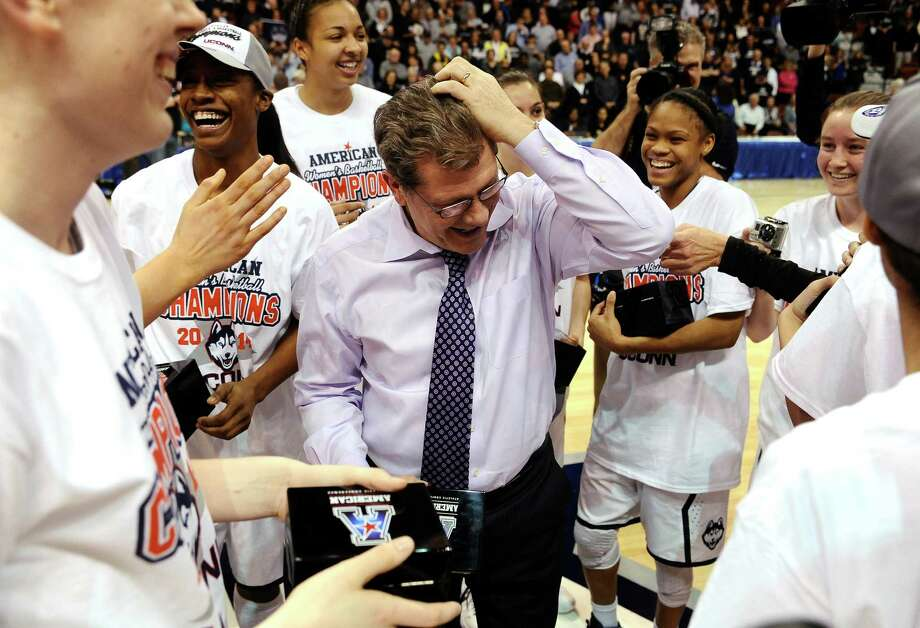 Connecticut head coach Geno Auriemma, center, fixes his hair after his team jokingly messed with it after winning the finals of the American Athletic Conference women's NCAA college basketball game against Louisville, Monday, March 10, 2014, in Uncasville, Conn. Connecticut won 72-52. Photo: Jessica Hill, AP / Associated Press