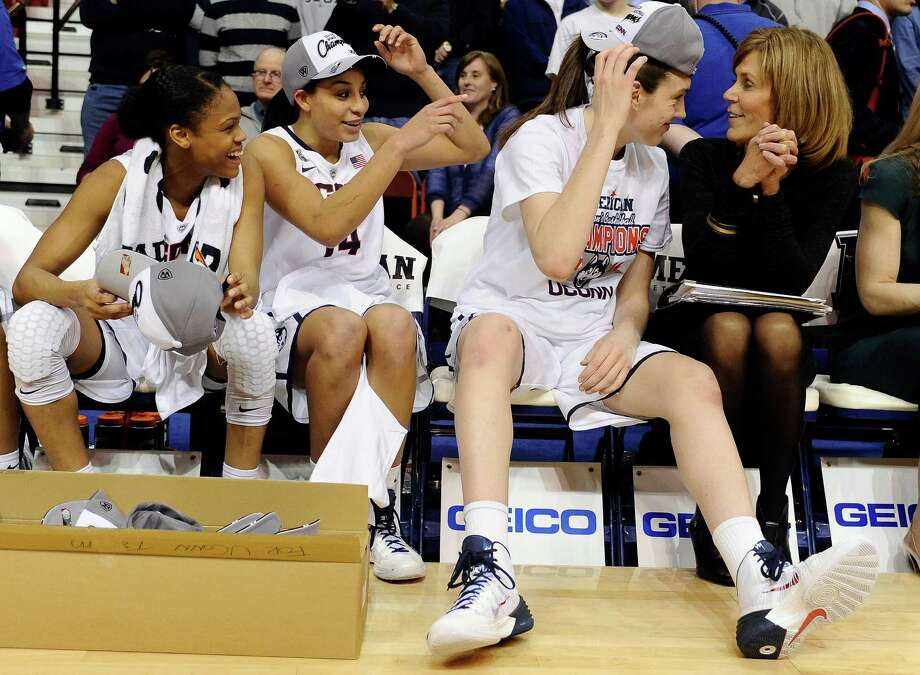 Connecticut's Breanna Stewart, second from right, looks to associate head coach Chris Dailey, right, while playfully adjusting her cap as teammates Moriah Jefferson, left, and Bria Hartley, second from left, look on after winning an NCAA college basketball game in the finals of the American Athletic Conference women's basketball tournament against Louisville, Monday, March 10, 2014, in Uncasville, Conn. Connecticut won 72-52. Photo: Jessica Hill, AP / Associated Press