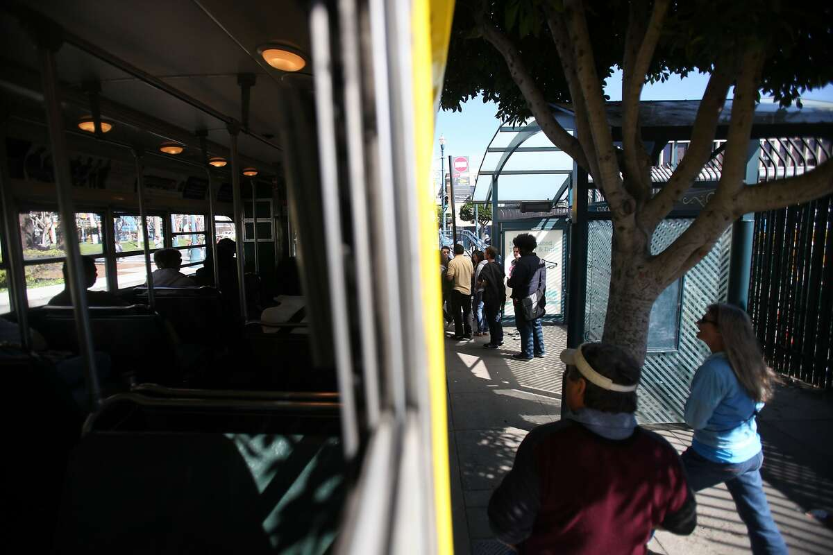 People on the Embarcadero line up to board Muni's F line of historic street cars in San Francisco, Calif. on March 10, 2014.