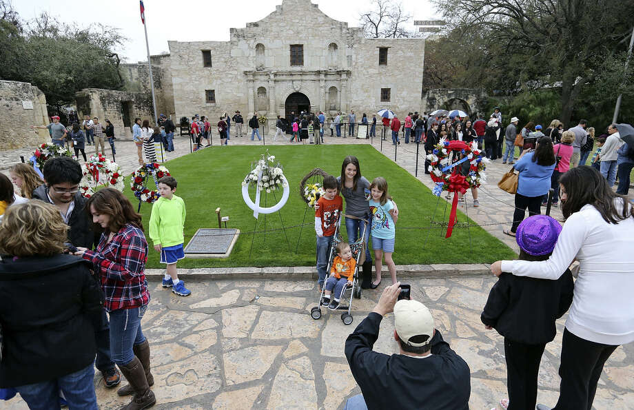 Visitors line the walkways at the Alamo before afternoon showers sent crowds scattering. Photo: Edward A. Ornelas / San Antonio Express-News / © 2014 San Antonio Express-News