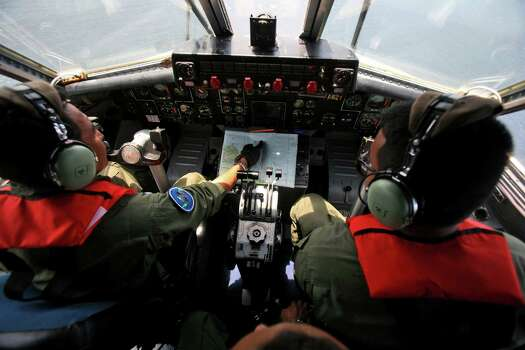 Indonesian Navy Maj. Bambang Edi Saputro, left, and 2nd Lt. Tri Laksono check their map during a search operation Monday, March 10, 2014, over the waters bordering Indonesia, Malaysia and Thailand near the Malacca straits. Photo: Binsar Bakkara / AP