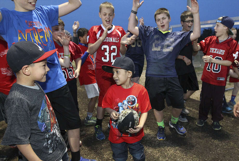 Mays Family YMCA Young Texans football players cheer Andy Pardo after they helped him run for a touchdown Friday. Photo: Photos By Kin Man Hui / San Antonio Express-News / ©2013 San Antonio Express-News