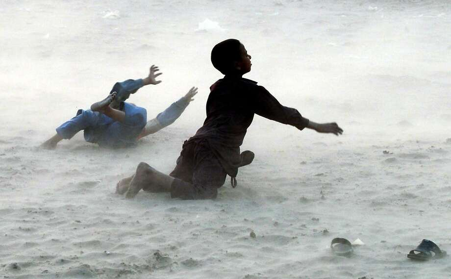 Wind-whipped in Lahore:Pakistani children enjoy the sensation of being sandblasted during a dust storm on the banks of the Ravi River. Photo: Arif Ali, AFP/Getty Images
