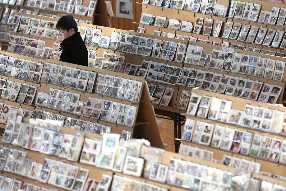 A young man looks through photographs, which were repaired after being washed away by the earthquake and tsunami at a gymnasium March 10, 2014 in Sendai, Miyagi prefecture, Japan. On March 11 Japan commemorates the third anniversary of the magnitude 9.0 earthquake and tsunami that claimed more than 18,000 lives, and subsequent nuclear disaster at the Fukushima Daiichi Nuclear Power Plant.  Photo: Yuriko Nakao, Getty Images