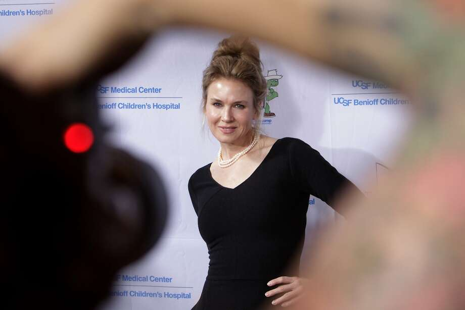"Renee Zellweger is seen through a photographer's arm as she poses on the red carpet as celebrities arrived for the Painted Turtle and UCSF Medical Center benefit, ""A Starry Evening of Music Comedy, and Surprises,"" at Davies Symphony Hall in San Francisco, Calif., on Monday, March 10, 2014. Photo: Carlos Avila Gonzalez, The Chronicle"