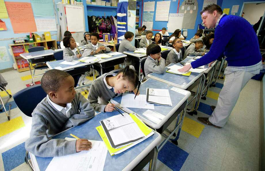 Students, including Tyheen Williams, far left, and Vanessa Powell on his right, work on reading at Bronx Charter School for Excellence in New York on Thursday, March 6, 2014. The school has filed an application to open Stamford Charter School for Excellence in 2015. Photo: Lindsay Perry / Stamford Advocate
