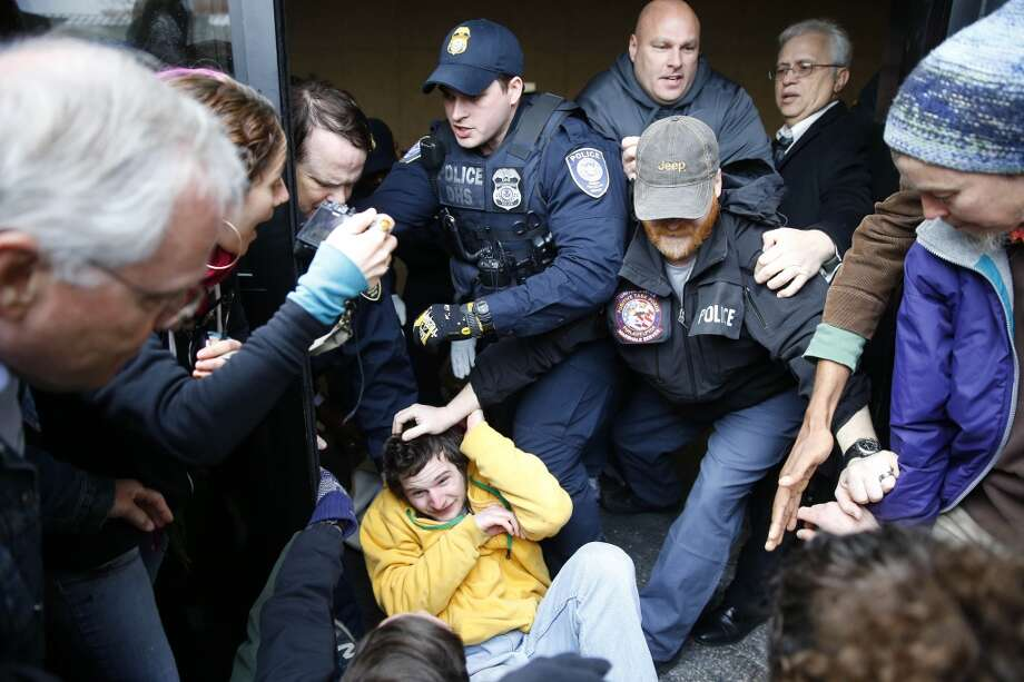 Police scuffle with protesters demonstrating in opposition to the proposed Keystone XL oil pipeline, Monday, March 10, 2014, as they block a door to the federal building in Philadelphia. The protestors say the pipeline would contribute to global warming. (AP Photo/Matt Rourke) Photo: Matt Rourke, AP