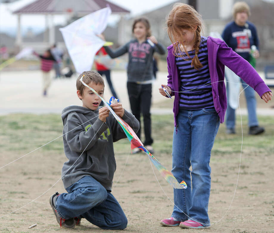 Josh Seaver, 8, left, works to untangle Angelica Barlow's kite during the first Kite Day at Huebner Elementary. Photo: Photos By Marvin Pfeiffer / Stone Oak Weekly / Express-News 2014