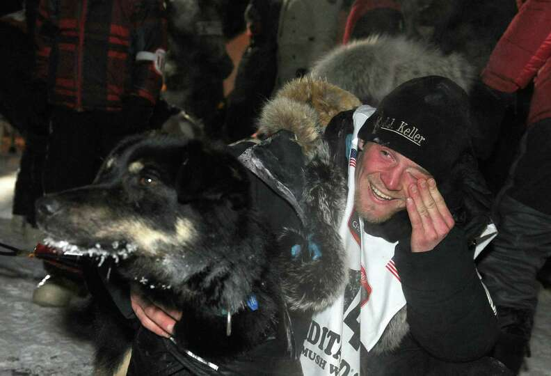 Dallas Seavey with his lead dog Beatle after crossing under the burled arch in Nome, Alaska to win t