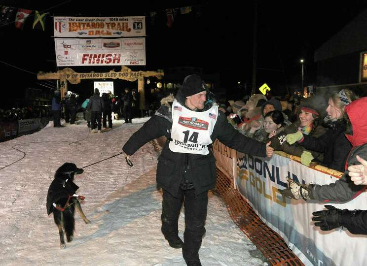 Dallas Seavey greets the crowd after crossing under the burled arch in Nome, Alaska to win the 2014