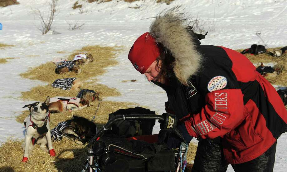 Iditarod musher Aliy Zirkle, from Two Rivers, Alaska, works on her gear at the White Mountain checkpoint during the 2014 Iditarod Trail Sled Dog Race on Monday, March 10, 2014. Zirkle has her out time for the checkpoint written on her finger. (AP Photo/The Anchorage Daily News, Bob Hallinen) Photo: Bob Hallinen, Associated Press / Anchorage Daily News