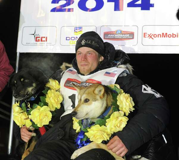 Dallas Seavey sits under the burled arch in Nome, Alaska to win the 2014 Iditarod Trail Sled Dog Rac
