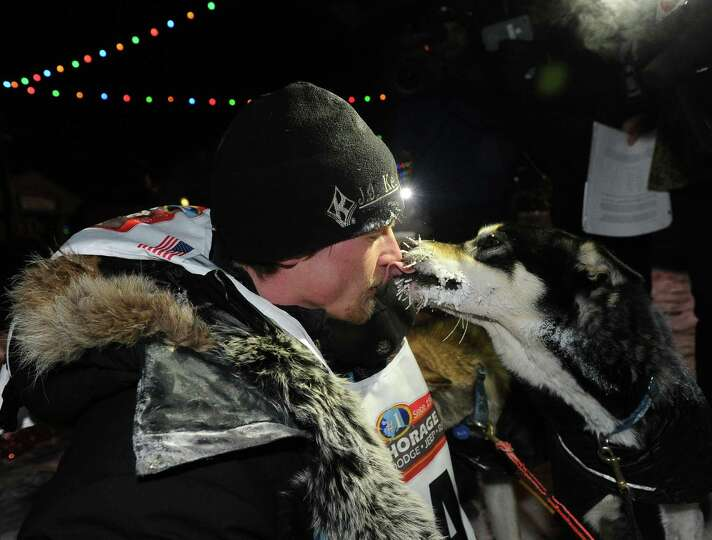 Dallas Seavey gets a kiss from one of his dogs after crossing under the burled arch in Nome, Alaska