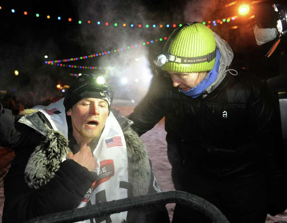 An exhausted Dallas Seavey collapsed on the back of sled after crossing under the burled arch in Nome, Alaska to win the 2014 Iditarod Trail Sled Dog Race on Tuesday, March 11, 2014. Dallas' wife Jen Seavey, right, greets him at the finish line.  (Bob Hallinen/Anchorage Daily News/MCT) Photo: Bob Hallinen, McClatchy-Tribune News Service / Anchorage Daily News