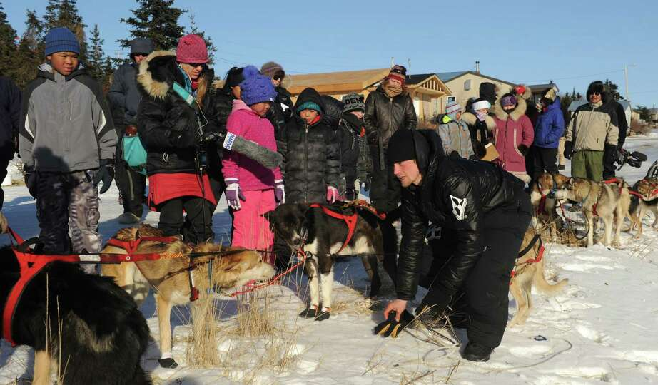 Villagers watch as Dallas Seavey, from Willow, AK, cares for his dog team after arriving in Koyuk ch