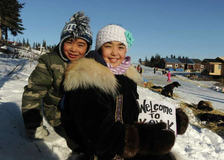 Harald Nassuk and his sister Tara Nassuk, who holds a sign welcoming the mushers to Koyuk, pose for