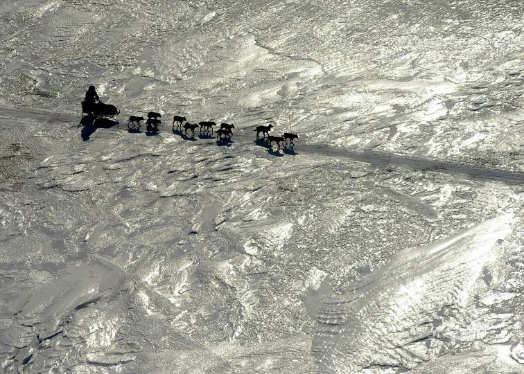 An Iditarod musher crosses the ice between the Shaktoolik and Koyuk checkpoints during the 2014 Idit