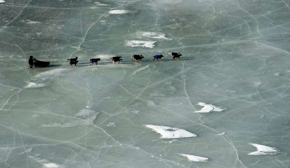 An Iditarod musher crosses a frozen pond between the Shaktoolik and Koyuk checkpoints during the 201