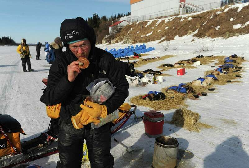 Iditarod musher Mitch Seavey, from Seward, Alaska, has a ginger snap cookie after caring for his dog