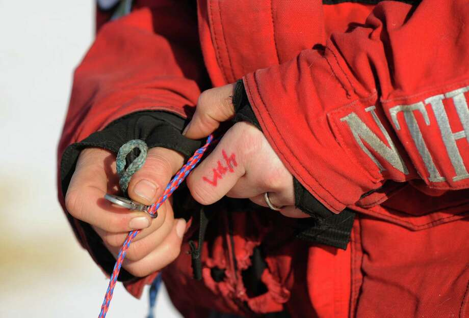 Iditarod musher Aliy Zirkle, from Two Rivers, Alaska, works on her gear at the White Mountain checkpoint during the 2014 Iditarod Trail Sled Dog Race on Monday, March 10, 2014. Zirkle has her out time for the checkpoint written on her finger. (AP Photo/The Anchorage Daily News, Bob Hallinen) ORG XMIT: AKAND203 Photo: Bob Hallinen, AP / Anchorage Daily News