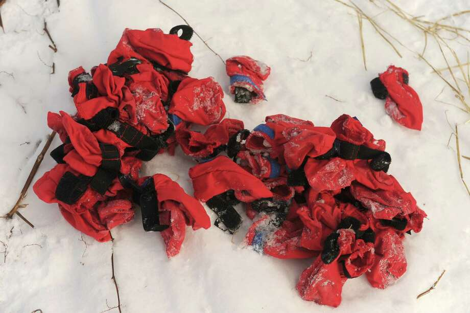 A pile of dog booties lies on the snow near the dog team belonging to Mats Pettersson, of Sweden, at the Takotna, Alaska, checkpoint during the Iditarod Trail Sled Dog Race on Wednesday, March 5, 2014. (AP Photo/Anchorage Daily News, Bob Hallinen) ORG XMIT: AKAND324 Photo: Bob Hallinen, AP / Anchorage Daily News