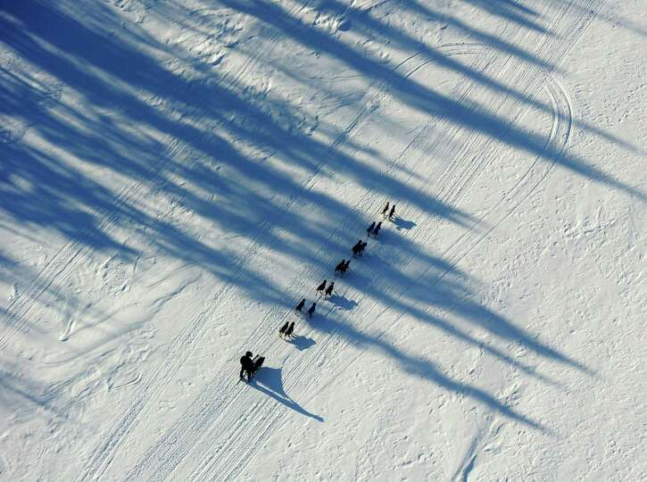 An Iditarod musher drives his team down the Yukon River after leaving the Ruby checkpoint and headin