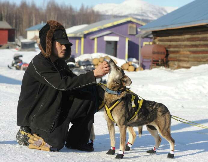 Frederick Huntington visits with one of Hans Gatt's dogs after he arrived into the Yukon River villa