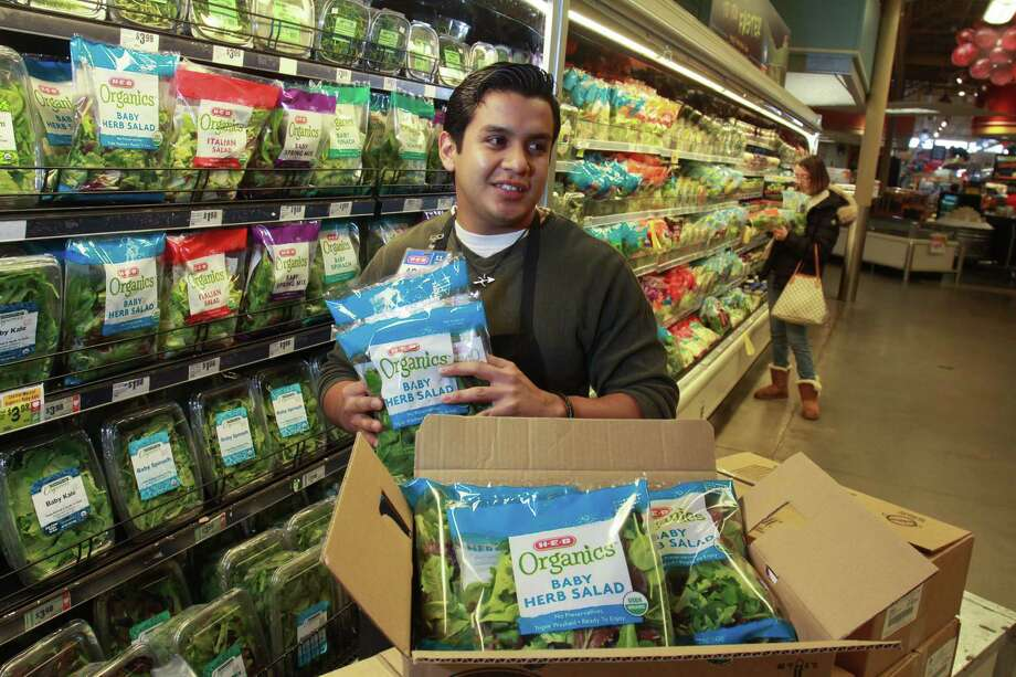 Adam Martinez, produce manager at H-E-B Bunker Hill Market, stocks H-E-B Organics salad blends, part of the chain's new line. Photo: Gary Fountain, Freelance / Copyright 2014 Gary Fountain.