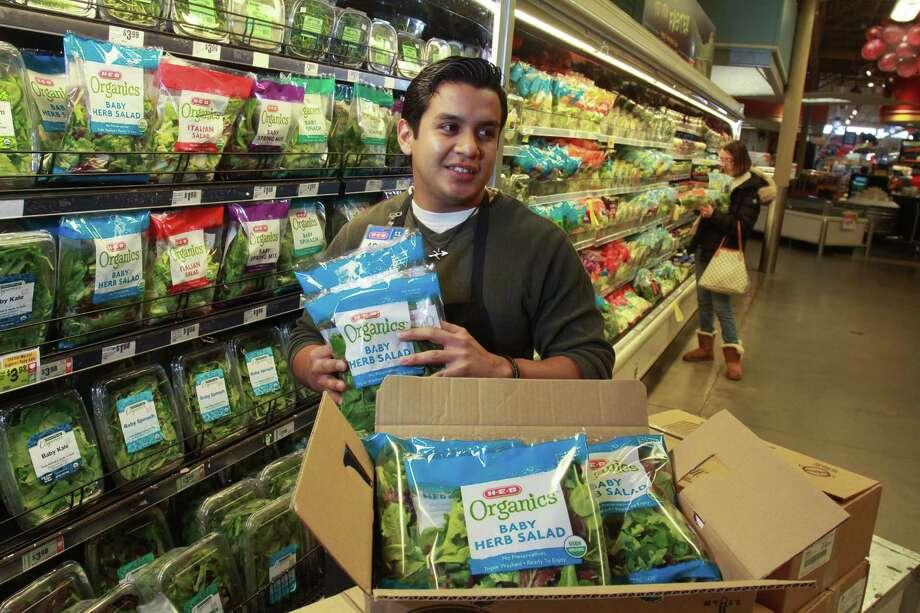 Adam Martinez, produce manager at H-E-B Bunker Hill Market, stocks H-E-B Organics salad blends, part of the chain's new line. Photo: Gary Fountain, Freelance / Copyright 2014 Gary Fountain.