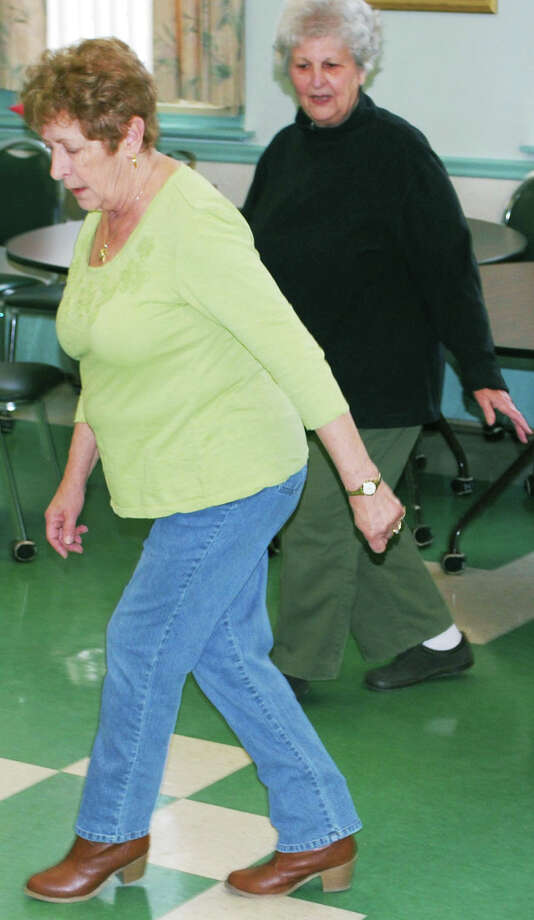 Rita Hull, left, and Grace Panetta kick off with a Bartender Stomp dance at a recent line dancing class at the New Milford Senior Center, March 10, 2014. Photo: Deborah Rose / The News-Times