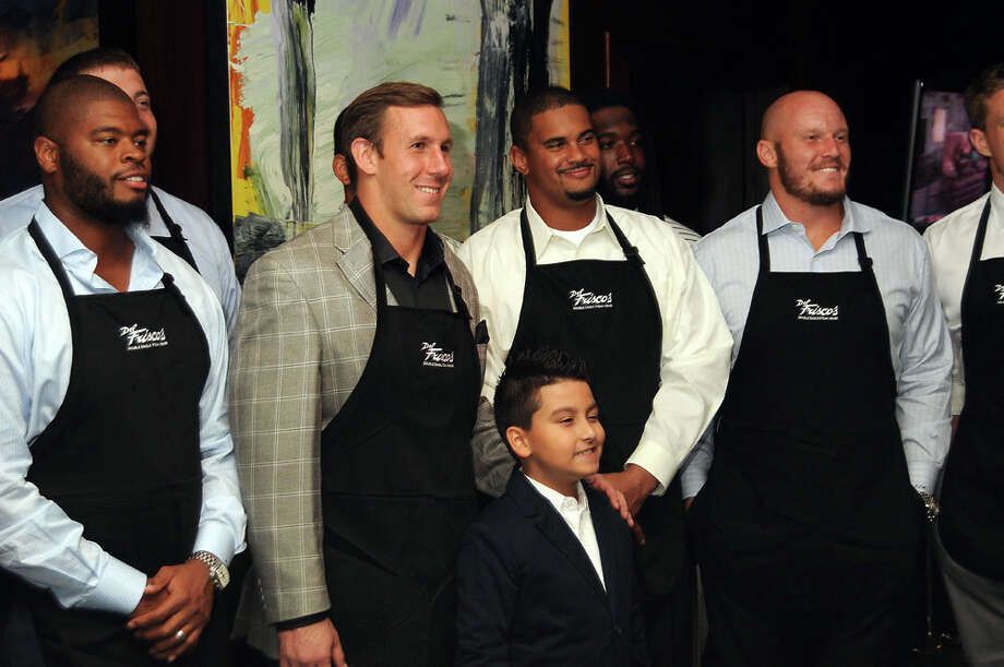 Owen Daniles poses with George Michalec,11, and some of his teammates at the Fourth Annual Celebrity Waiter Night hosted by Daniels and benefitting the Owen Daniels Catching Dreams Foundation at Del Frisco's Double Eagle Steak House Sept. 16 2013. Photo: Dave Rossman, For The Houston Chronicle / © 2013 Dave Rossman