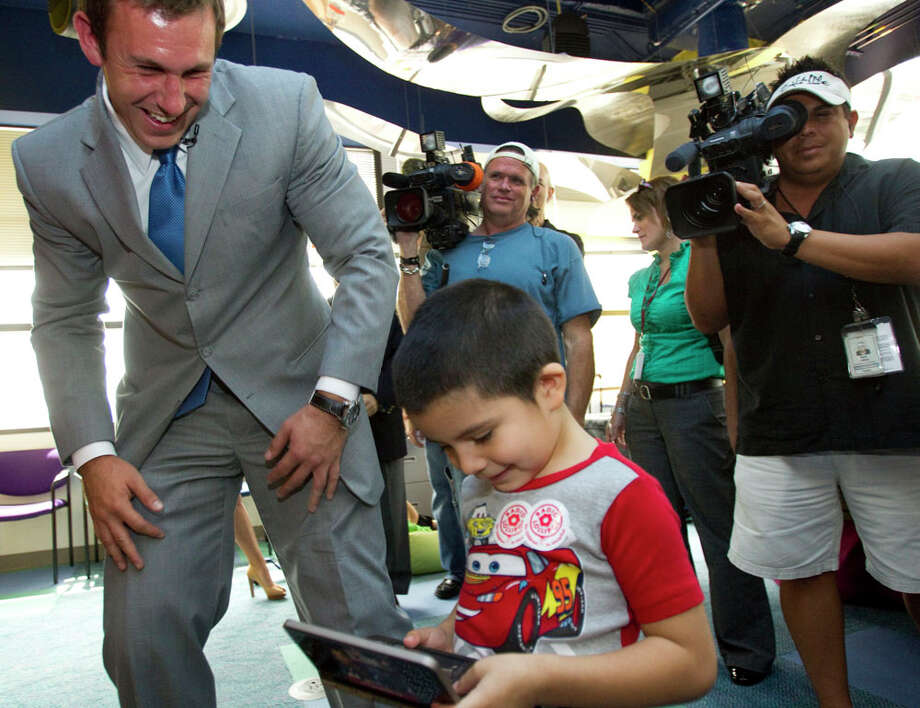 "Houston Texans tight end Owen Daniels, left, smiles after handing a game to patient Hesiquio Cabrera, 5, during an unveiling ceremony for Owen's Locker at Texas Children's Hospital  June 22, 2011, in Houston. The ""Locker"" put together on behalf of Daniels' Catch a Dream Foundation, is designed to enrich the lives of patients by providing them and their families access to notebook computers, DVD players, gaming systems and other items to help pass the time while undergoing treatment and recovery. The initial items for ""Owen's Lockers"" at Texas Children's Hospital were purchased through generous donations from Walmart. Photo: Brett Coomer, Houston Chronicle / © 2011 Houston Chronicle"