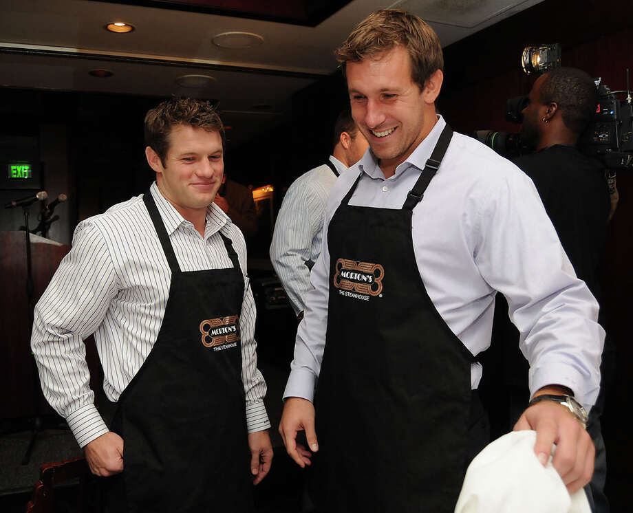 Houston Texans David Anderson and Owen Daniels prepare to serve guests during a fundraiser for the Catch a Dream Foundation at Morton's Steakhouse Aug. 30, 2010. Photo: Dave Rossman, For The Chronicle / Freelance