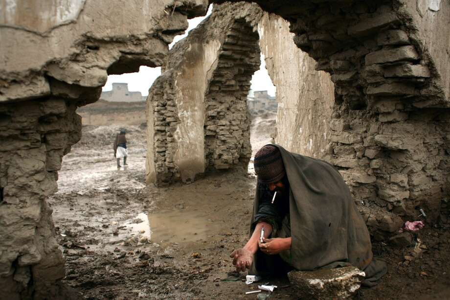 An addict injects himself with heroin among the ruins of the old part of Kabul, Afghanistan, on march 11, 2007. Long cloistered by two decades of war and then the strict Islamic rule of the Taliban, Afghanistan was for many years shielded from the worst ravages of the AIDS pandemic. Not anymore. HIV and AIDS has quietly arrived in this land of thousand calamities. (Aaron Huey/Atlas Press via The New York Times)  **MAGS OUT/NO SALES** Photo: AARON HUEY/ATLAS PRESS, NYT