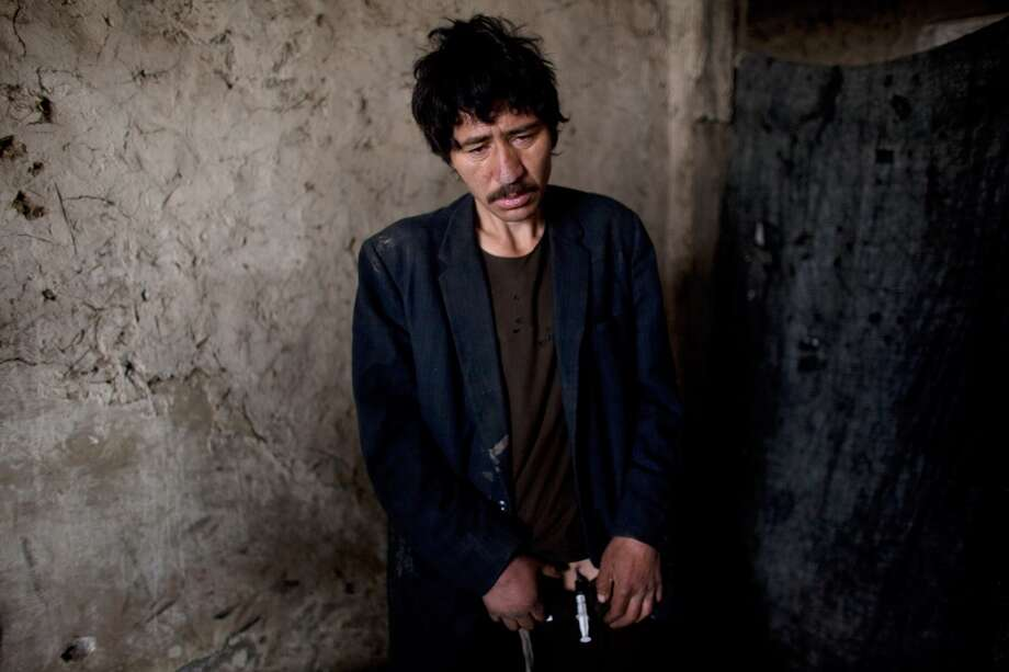 "A heroin addict injects the drug into his thigh inside the abandoned Russian Cultural center used as the heroin gathering point in the capitol city February 10, 2009 in Kabul, Afghanistan. Heroin addicts are on the increase in Kabul as the numbers of unemployed increase and the drug continues to be readily available and extremely cheap at only 50 afghany per hit or $1 USD. Afghanistan accounts for more than 90 per cent of the world's heroin supply. Its annual opium harvest is worth up to $3bn, or almost half the country's official gross domestic product. Profits from heroin fund the Taliban, along with corrupt Afghan officials who profit from it. Recently the Obama's US special envoy for Pakistan and Afghanistan, Richard Holbrooke stated that the US counter-narcotics effort in Afghanistan ""may be the single most ineffective program in the history of foreign policy."" Many Afghans have come back from Iran working in blue collar labor jobs already addicted. There are 1.6 million addicts in Iran according to the UN office on Drugs and Crime (UNODC) all dependent on the heroin supplies coming from neighboring Afghanistan.   (Photo by Paula Bronstein/Getty Images) Photo: Paula Bronstein, Getty Images"