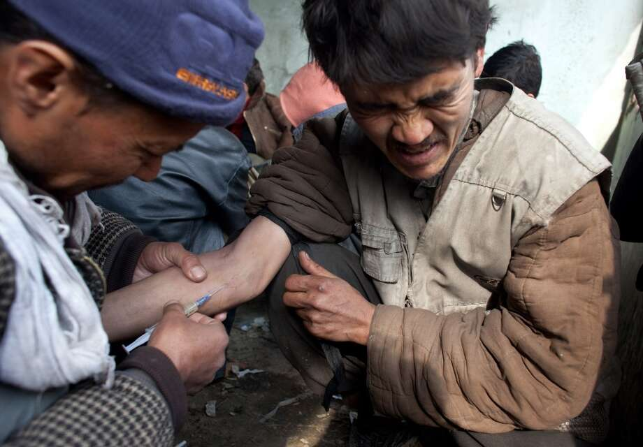 "A Heroin addict gets help injecting heroin at the abandoned Russian Cultural center which is used as the heroin gathering point in the capitol city February 09, 2009 in Kabul, Afghanistan. Heroin addicts are on the increase in Kabul as the numbers of unemployed increase and the drug continues to be readily available and extremely cheap at only 50 afghany per hit or $1 USD. Afghanistan accounts for more than 90 per cent of the world's heroin supply. Its annual opium harvest is worth up to $3bn, or almost half the country's official gross domestic product. Profits from heroin fund the Taliban, along with corrupt Afghan officials who profit from it. Recently the Obama's US special envoy for Pakistan and Afghanistan, Richard Holbrooke stated that the US counter-narcotics effort in Afghanistan ""may be the single most ineffective program in the history of foreign policy."" Many Afghans have come back from Iran working in blue collar labor jobs already addicted. There are 1.6 million addicts in Iran according to the UN office on Drugs and Crime (UNODC) all dependent on the heroin supplies coming from neighboring Afghanistan.   (Photo by Paula Bronstein/Getty Images) Photo: Paula Bronstein, Getty Images"
