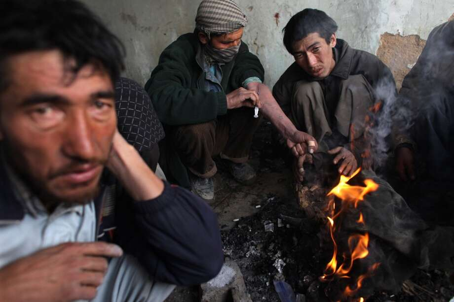 "Heroin addicts inject while keeping warm by  a fire inside the abandoned Russian Cultural center used as the heroin gathering point in the captiol city February 09, 2009 in Kabul, Afghanistan. Heroin addicts are on the increase in Kabul as the numbers of unemployed increase and the drug continues to be readily available and extremely cheap at only 50 afghany per hit or $1 USD. Afghanistan accounts for more than 90 per cent of the world's heroin supply. Its annual opium harvest is worth up to $3bn, or almost half the country's official gross domestic product. Profits from heroin fund the Taliban, along with corrupt Afghan officials who profit from it. Recently the Obama's US special envoy for Pakistan and Afghanistan, Richard Holbrooke stated that the US counter-narcotics effort in Afghanistan ""may be the single most ineffective program in the history of foreign policy."" Many Afghans have come back from Iran working in blue collar labor jobs already addicted. There are 1.6 million addicts in Iran according to the UN office on Drugs and Crime (UNODC) all dependent on the heroin supplies coming from neighboring Afghanistan.   (Photo by Paula Bronstein/Getty Images) Photo: Paula Bronstein, Getty Images"