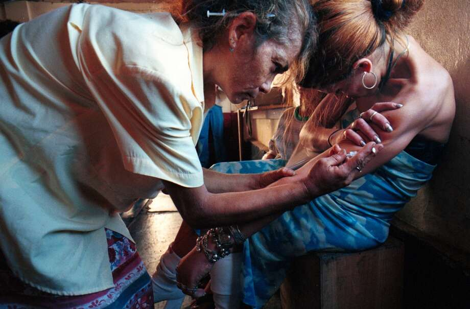 A heroin addict who did not want to be identified administers heroin to her friend in a 'shooting gallery' in San Juan, Puerto Rico Nov. 8, 2000.  Three decades after the war on drugs began, smuggling is at an all-time high, along with a rising tide of violent crime and corruption. Many people blame the war's heavy emphasis on interdiction and eradication over efforts to reduce demand. (AP Photo/ Tomas van Houtryve) *PUERTO RICO OUT* Photo: TOMAS VAN HOUTRYVE, AP